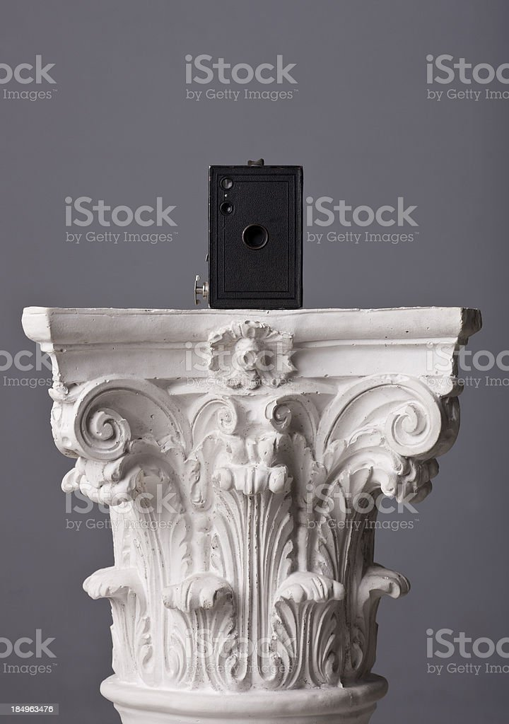 old box camera on a corinthian capital royalty-free stock photo