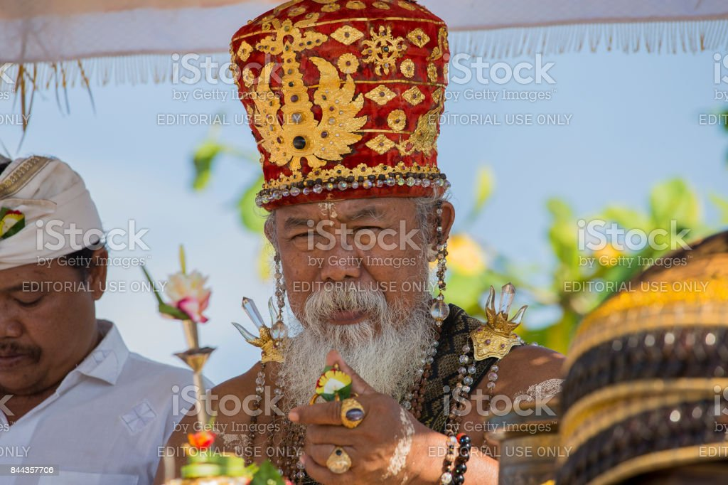 Old Brahmin conducts religious ritual on the beach Ketewel. Ubud, Bali,Indonesia stock photo