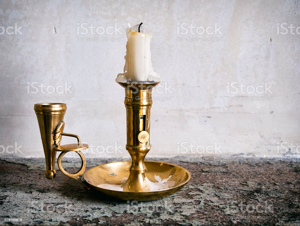 Old brass candlestick and snuffer on a shelf stock photo
