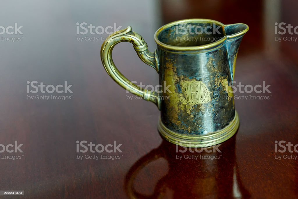 Old brass cup sitting on a glossy wood stock photo