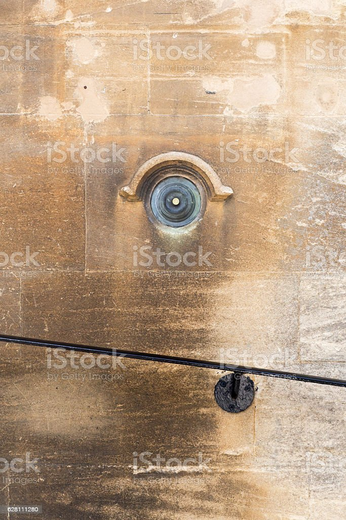 Old brass doorbell button on a beige stone wall stock photo
