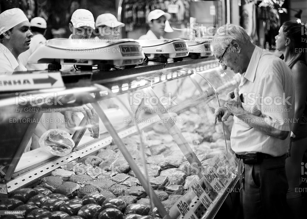 Old Brazilian man shopping at the butcher stock photo