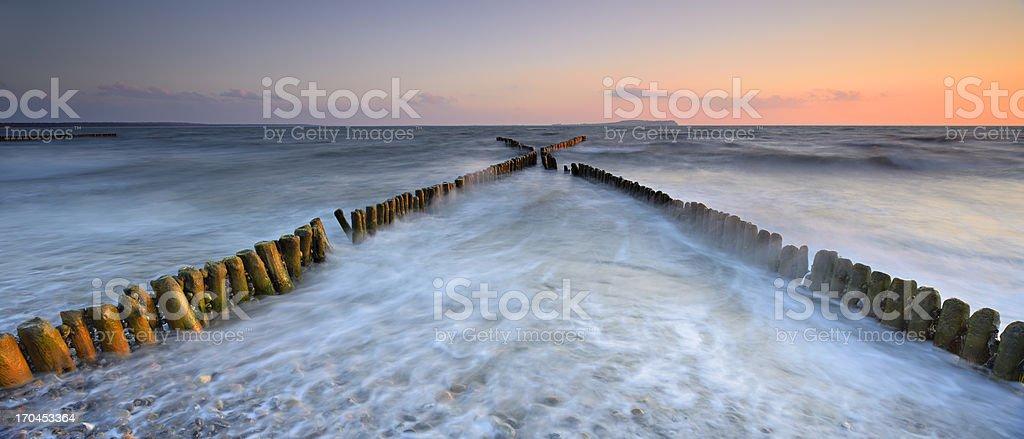 Old Breakwater on Beach at Sunset stock photo