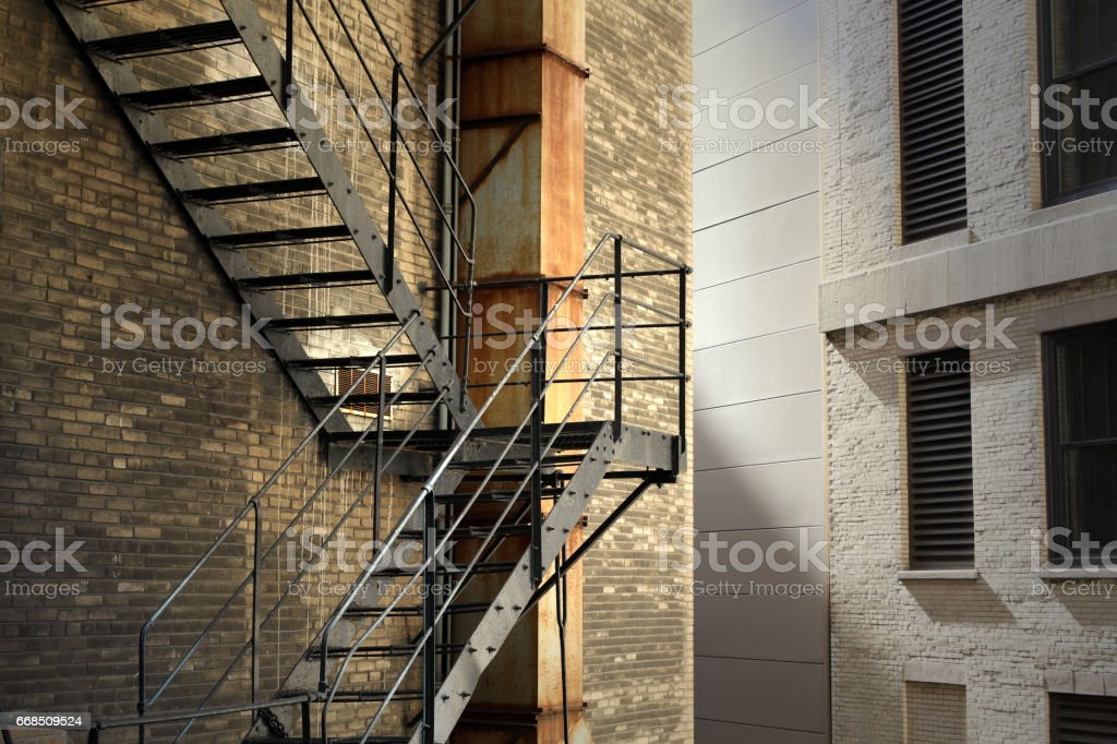 old brick building with fire escape stairs stock photo