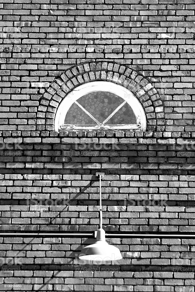 Old brick building with light and small divided window stock photo