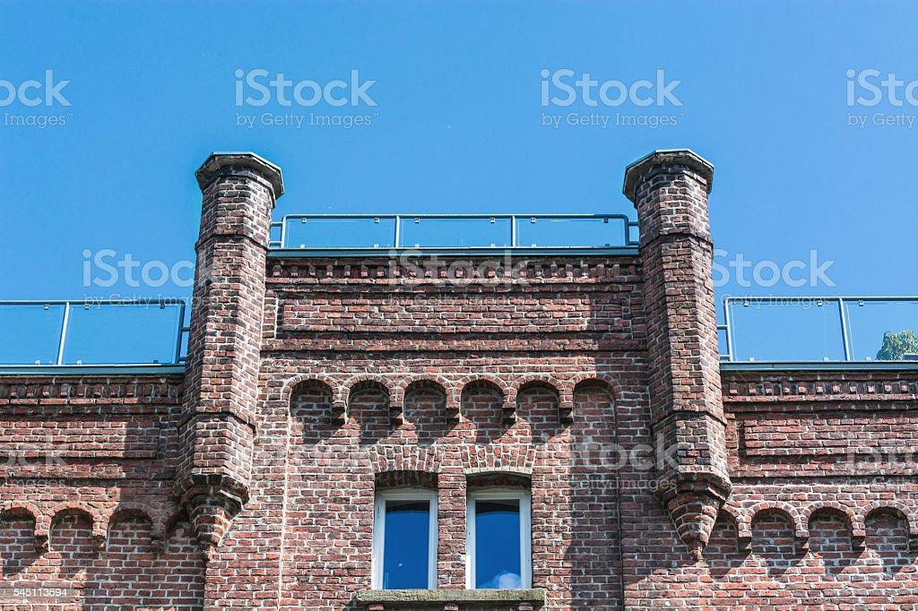 Old brick house against blue sky. stock photo