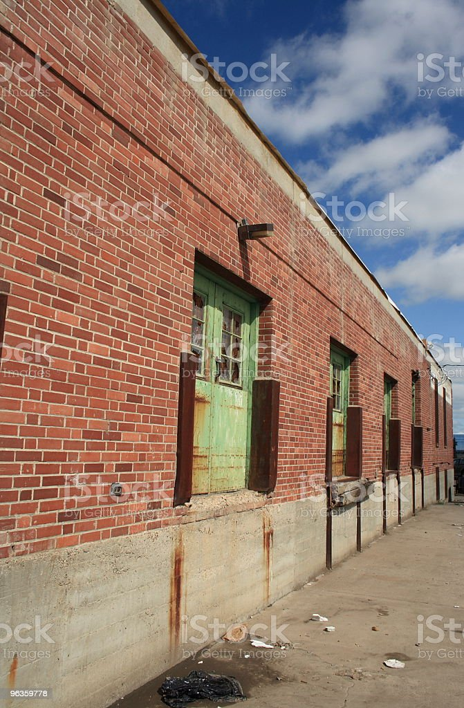old brick industrial building rusty green doors and windows royalty-free stock photo