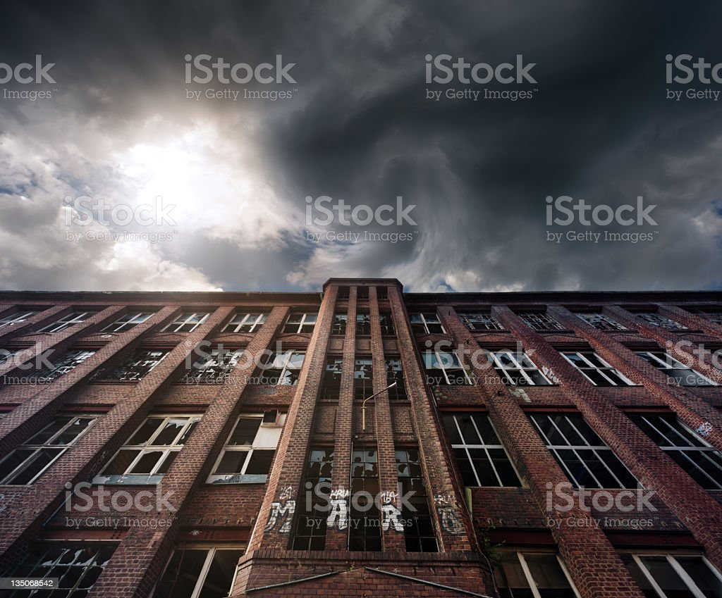 Old brick industrial building with dark clouded sky royalty-free stock photo