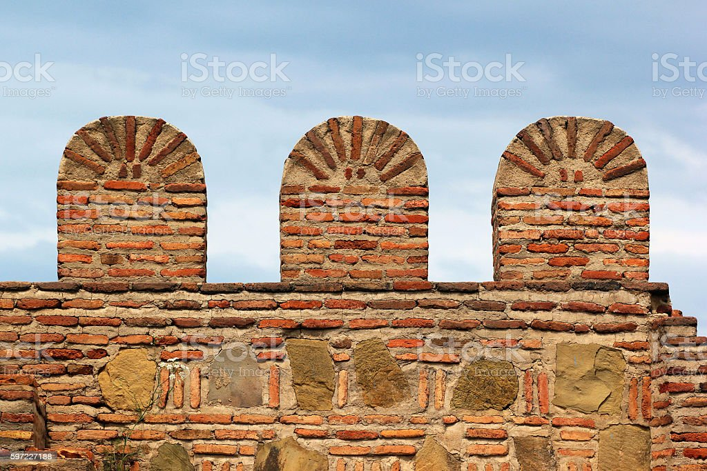 Old brick stone fortress wall with battlements stock photo