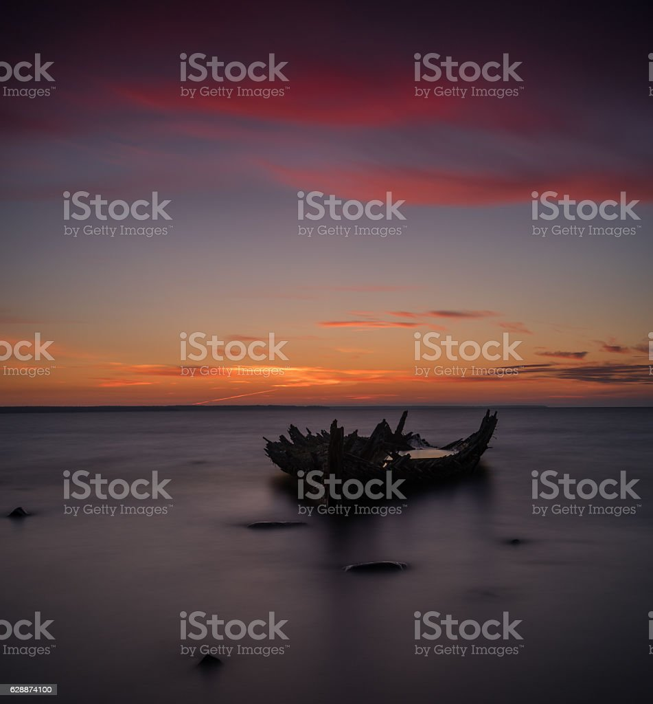 Old broken boat wreck, shore, frozen sea, red sunset background. stock photo