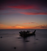 Old broken boat wreck, shore, frozen sea, red sunset background.