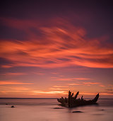 Old broken boat wreck, shore, soft sea, red sunset background.