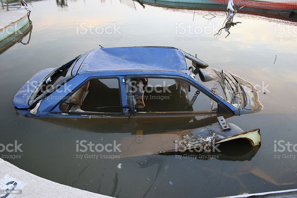 Old broken car submerged in water stock photo