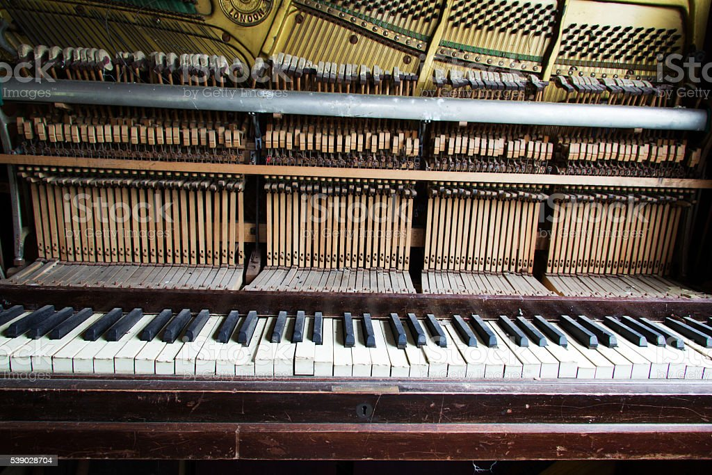 Old broken disused piano with damaged keys stock photo