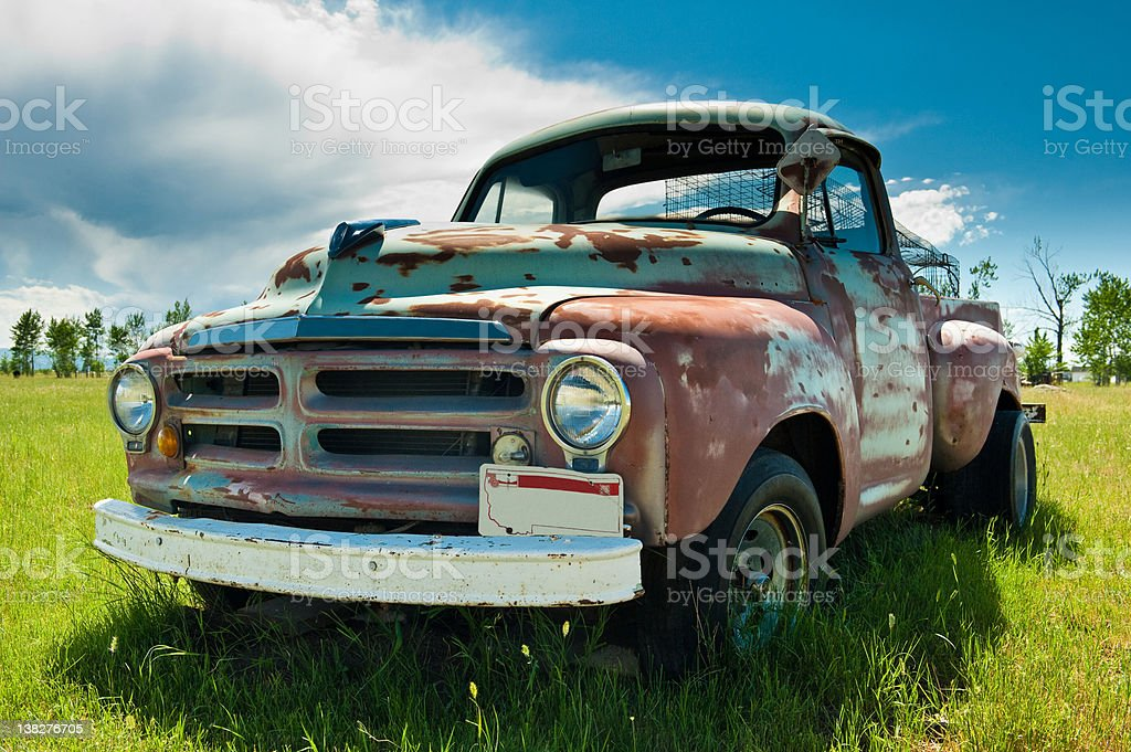 Old broken down pickup truck out in a field. stock photo