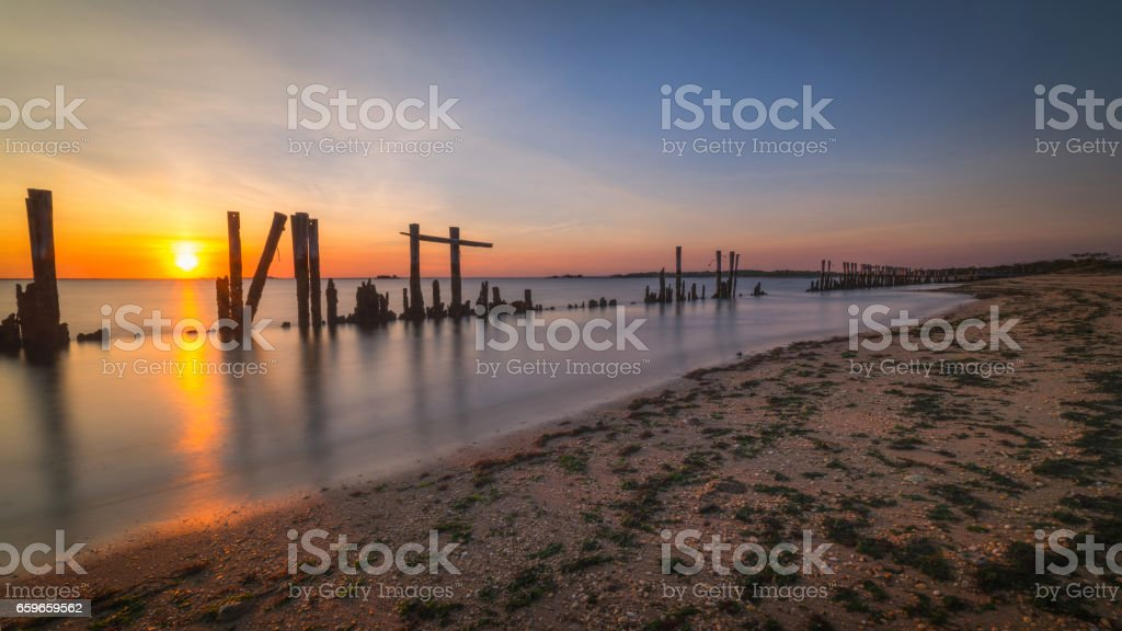Old broken pilings seascape sunset stock photo