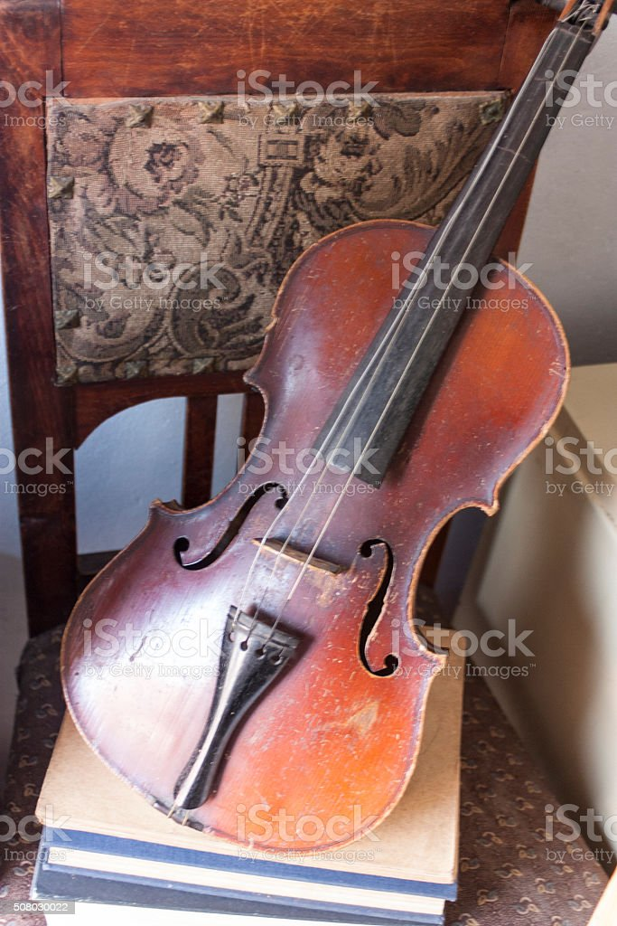 Old broken violin and sheet music papers on chair stock photo