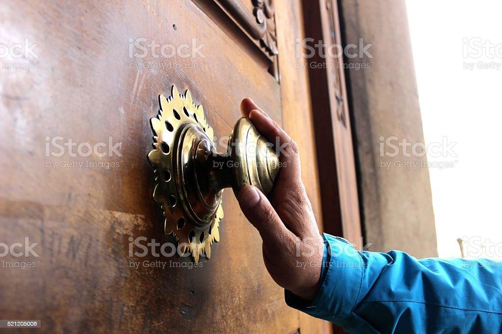 Old bronze door handle pushed by mans hand stock photo