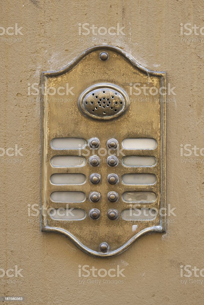 Old Bronze Entryphone on a Wall Background stock photo