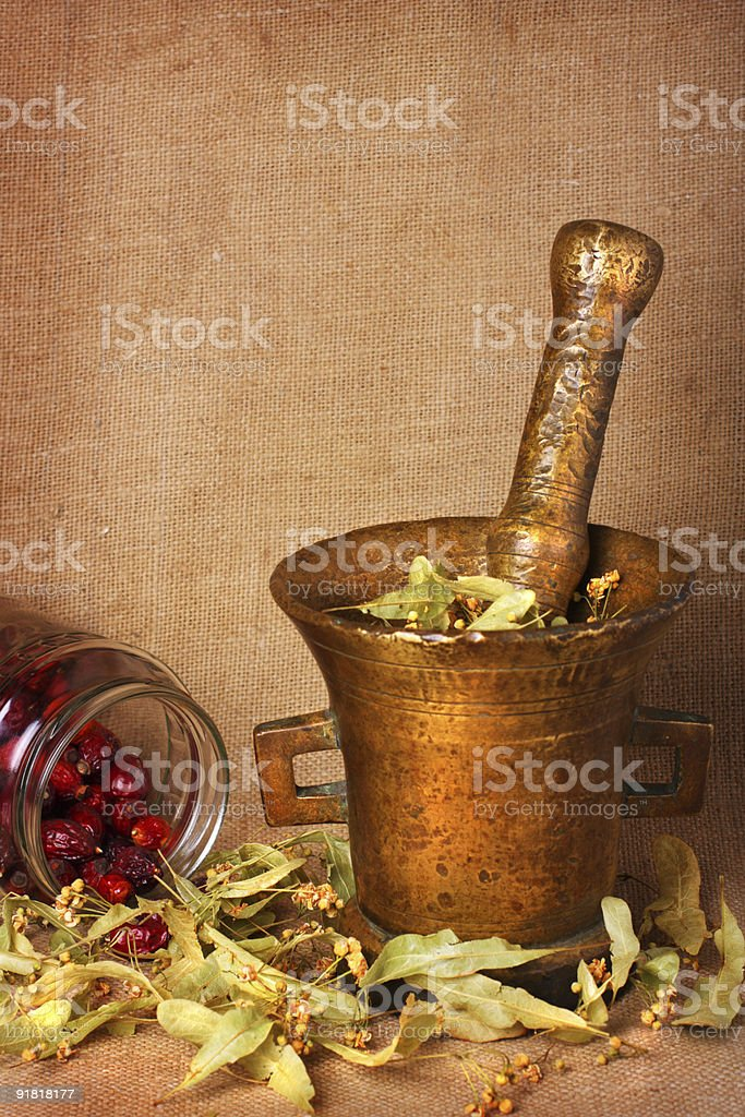 Old bronze mortar with herbs and rose hips royalty-free stock photo