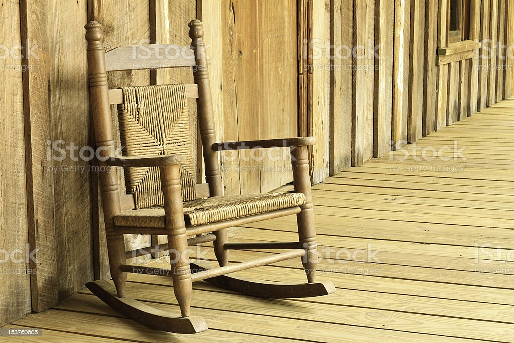 Old Brown Rocking Chair On Porch Of Wood Farmhouse stock photo