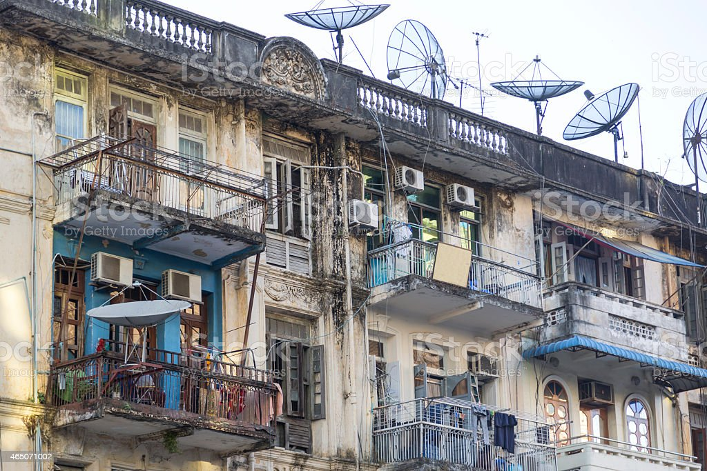 Old Building with AC and satellite dishes in central Yangon stock photo