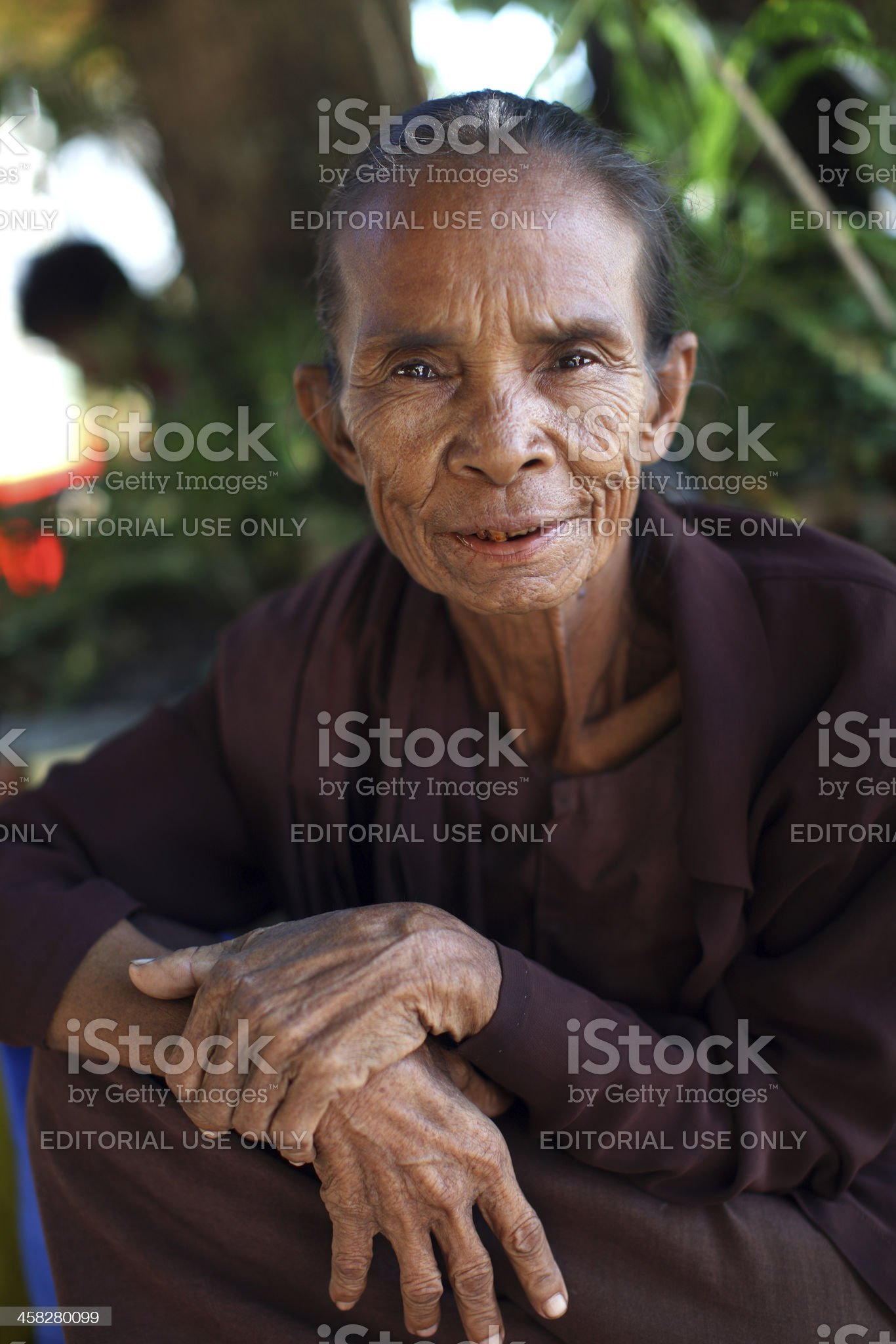 Old burmese woman in nuns robes, sitting by Pagoda, Myanmar royalty-free stock photo