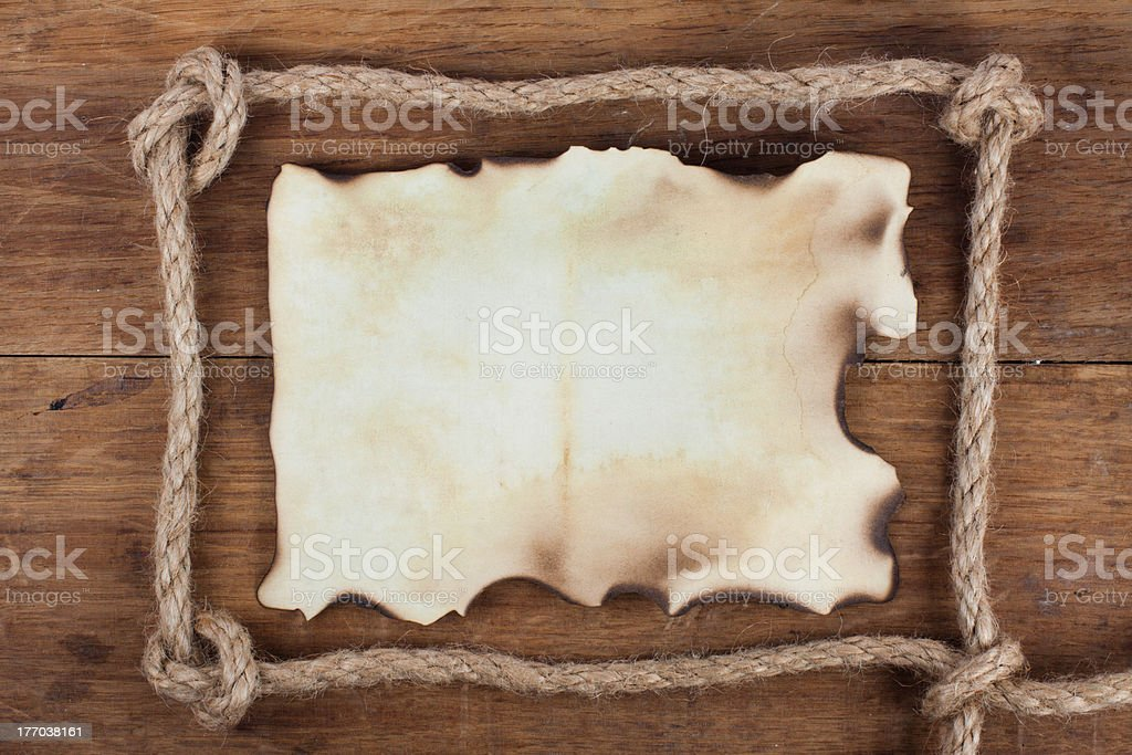 Old burnt paper in rope frame on wooden background stock photo