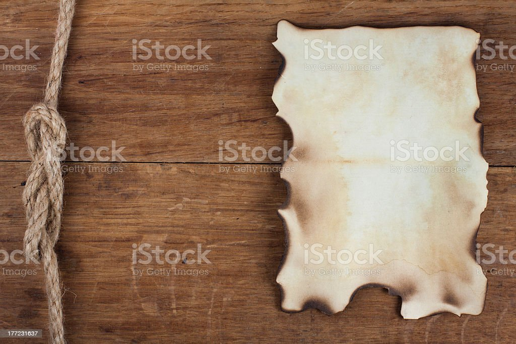Old burnt paper on wooden background stock photo