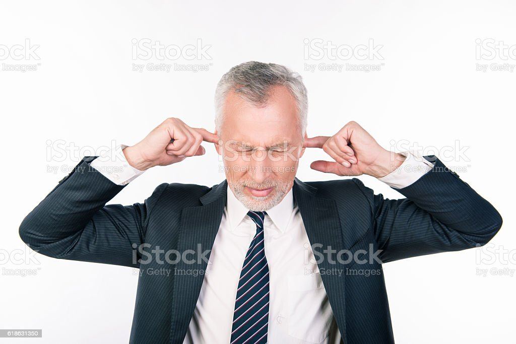 old businessman covering his ears, concept of business man stressed stock photo