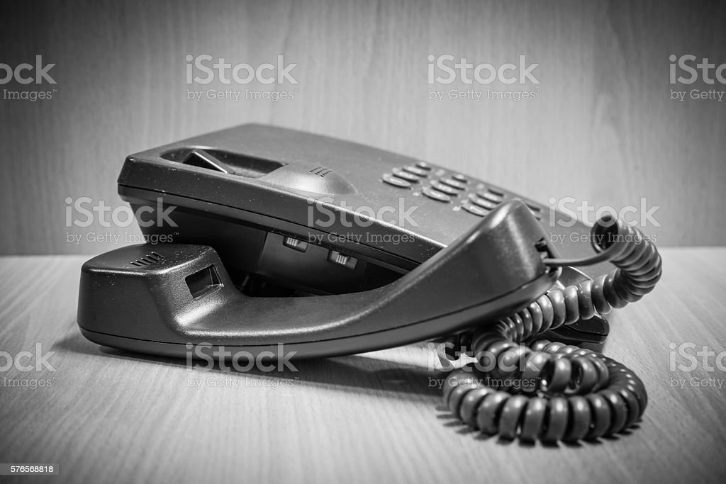Old button telephone on wooden desk stock photo