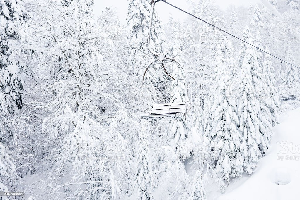 Old cable lift with no passengers going across coniferous forest stock photo