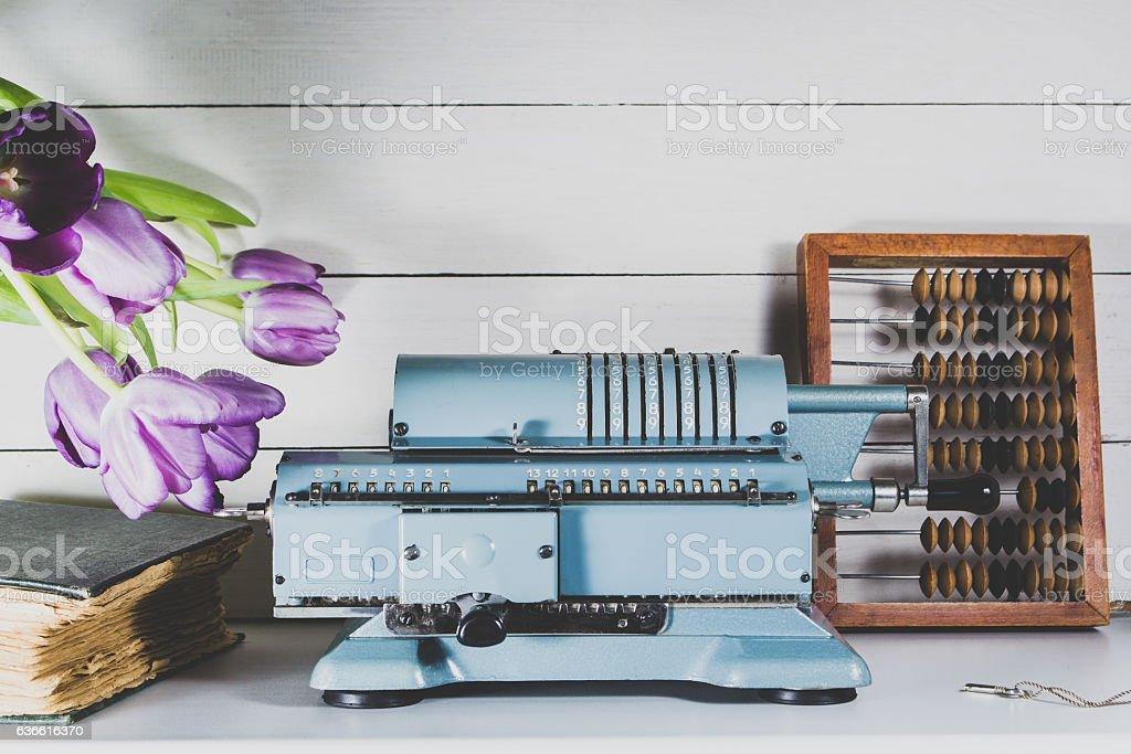 Old calculating machine on a wooden table stock photo