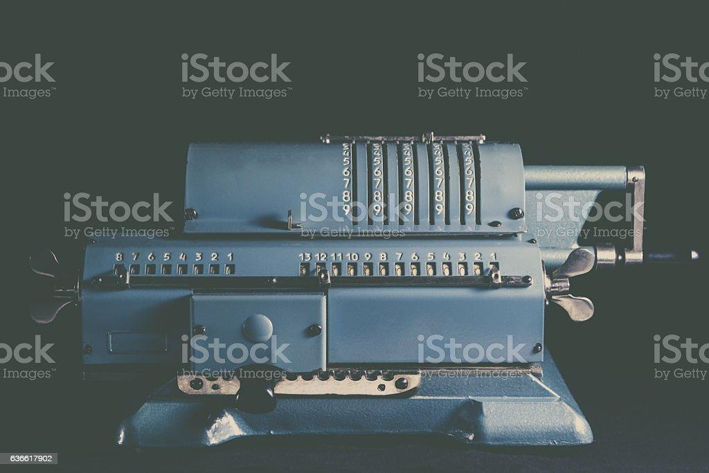 Old calculating machine on black background stock photo