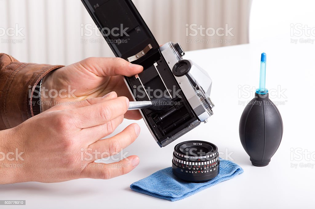 Old camera in male hands stock photo