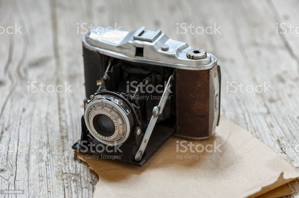 old camera on table of wood in foreground stock photo