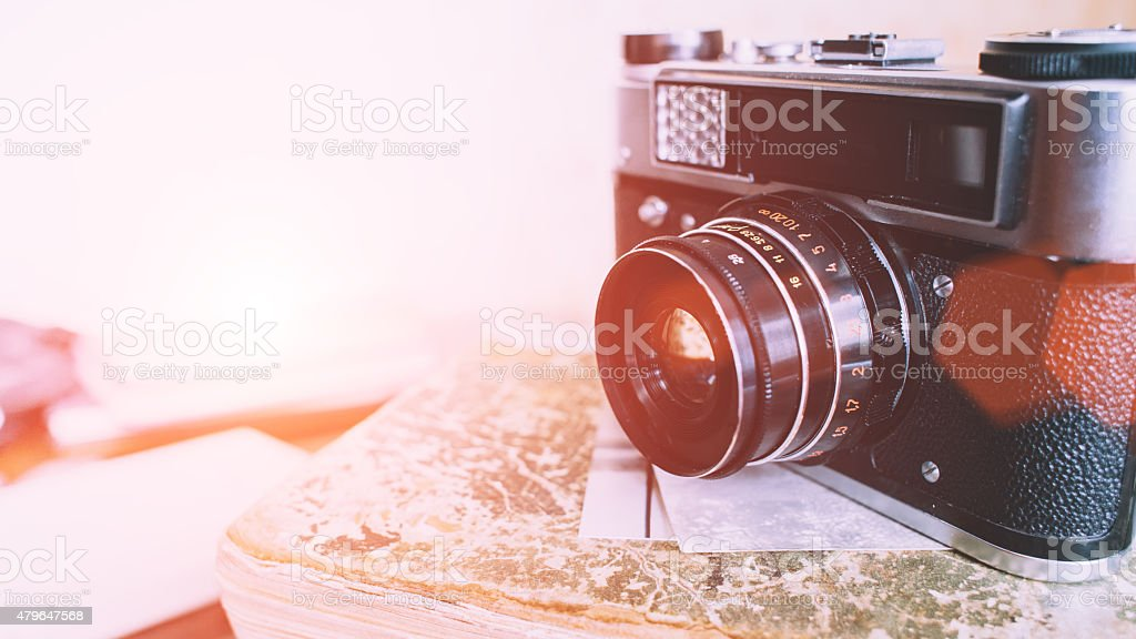 old camera over books stock photo