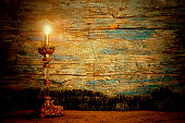 Old candle lit wooden background. Copy space