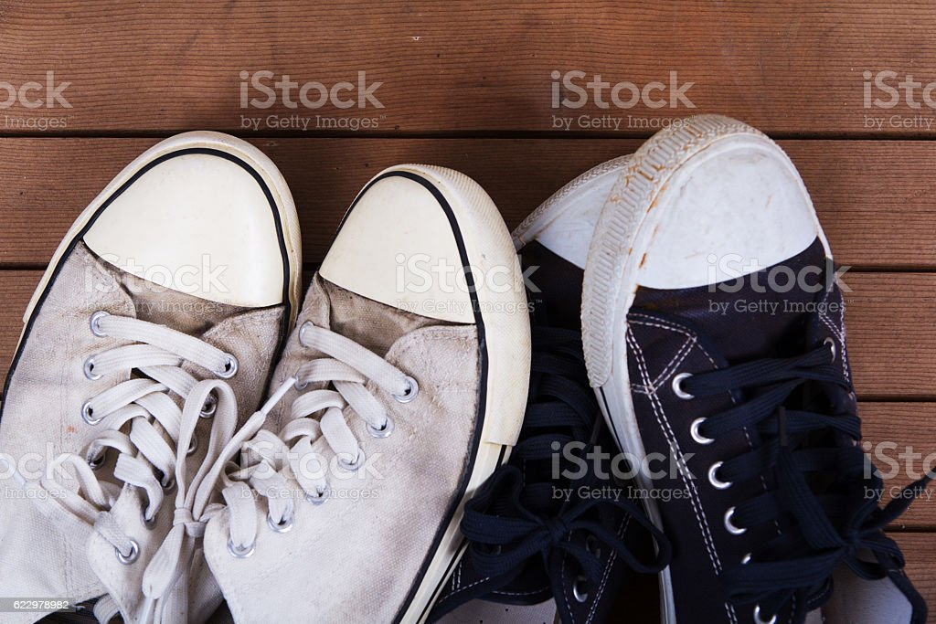 Old canvas shoes on a wooden floor stock photo