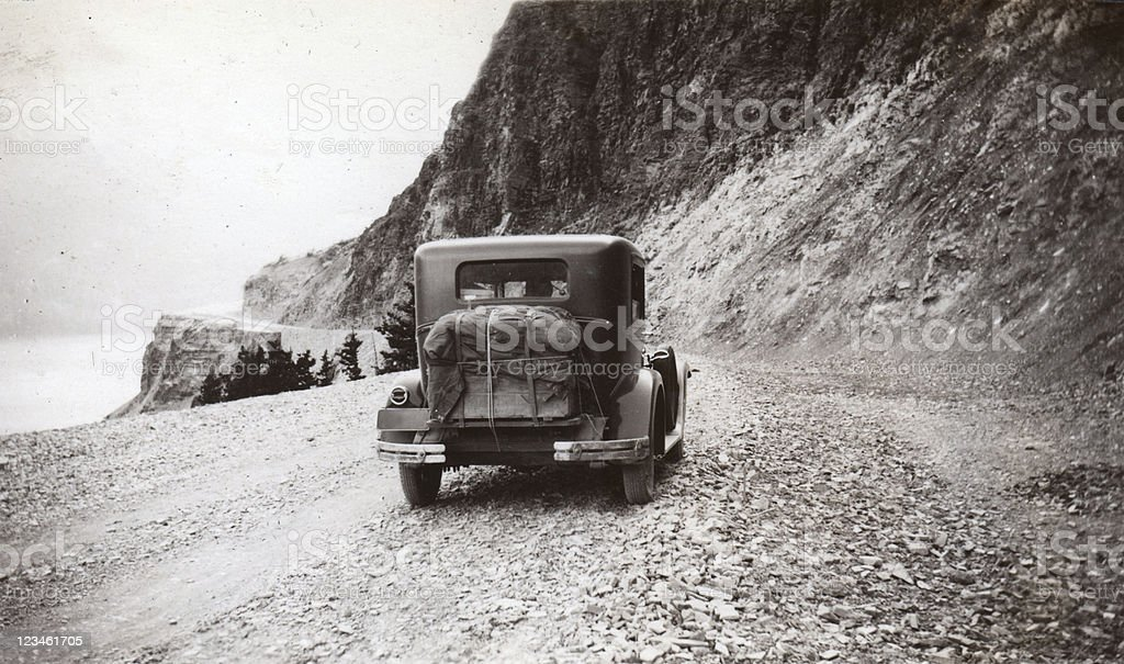 Old car driving to Logan Pass, Glacier Park royalty-free stock photo