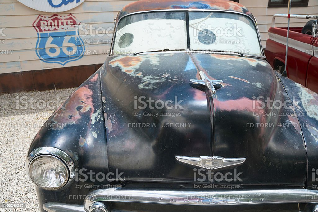 Old car looking at Route 66 sign royalty-free stock photo