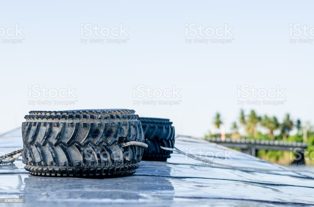 Old car tires on the boat in thai river stock photo