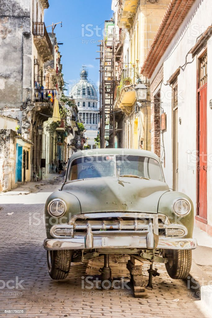 Old car under repair in the Old Havana streets of Cuba with Capitolio in background stock photo