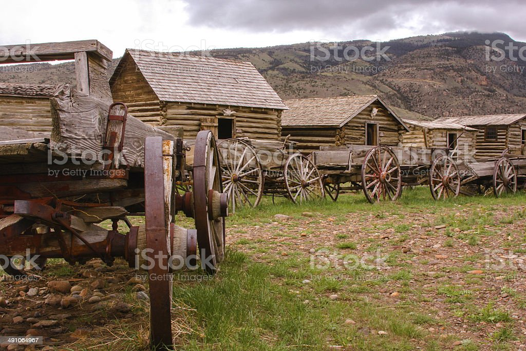 Old carriage wheel and wagons in a cloudy day stock photo
