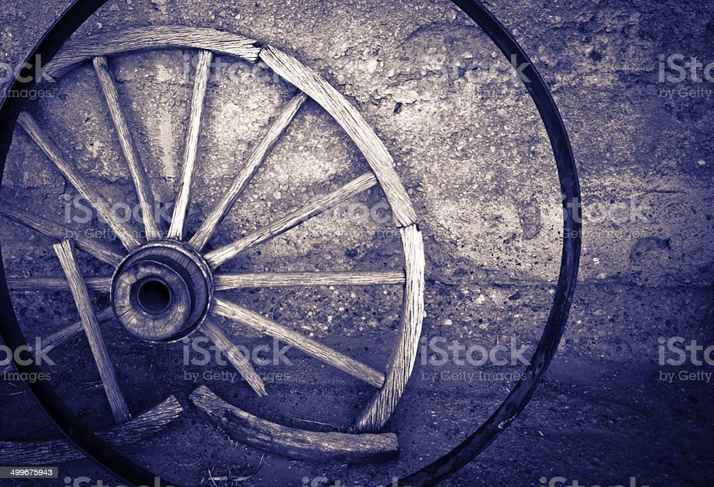 Old cart wheel against a wall royalty-free stock photo