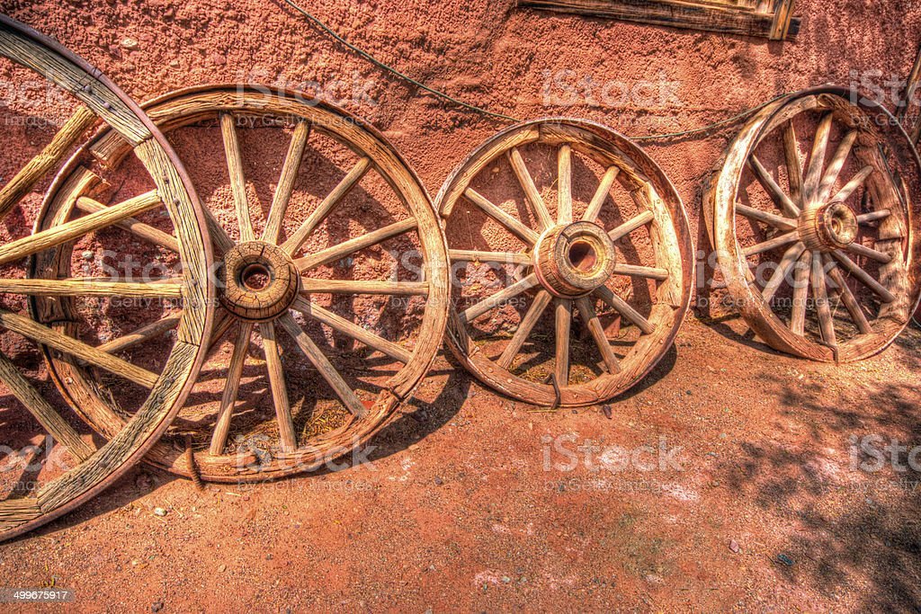 Old cart wheels against a wall royalty-free stock photo
