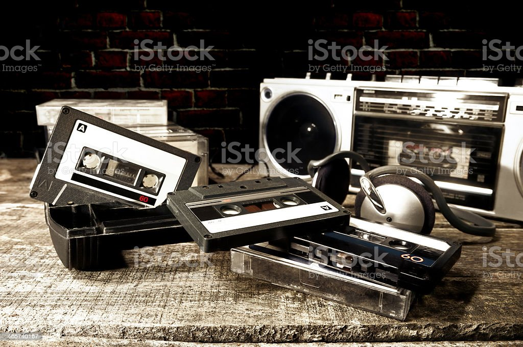Old cassette tapes and player on wooden surface stock photo