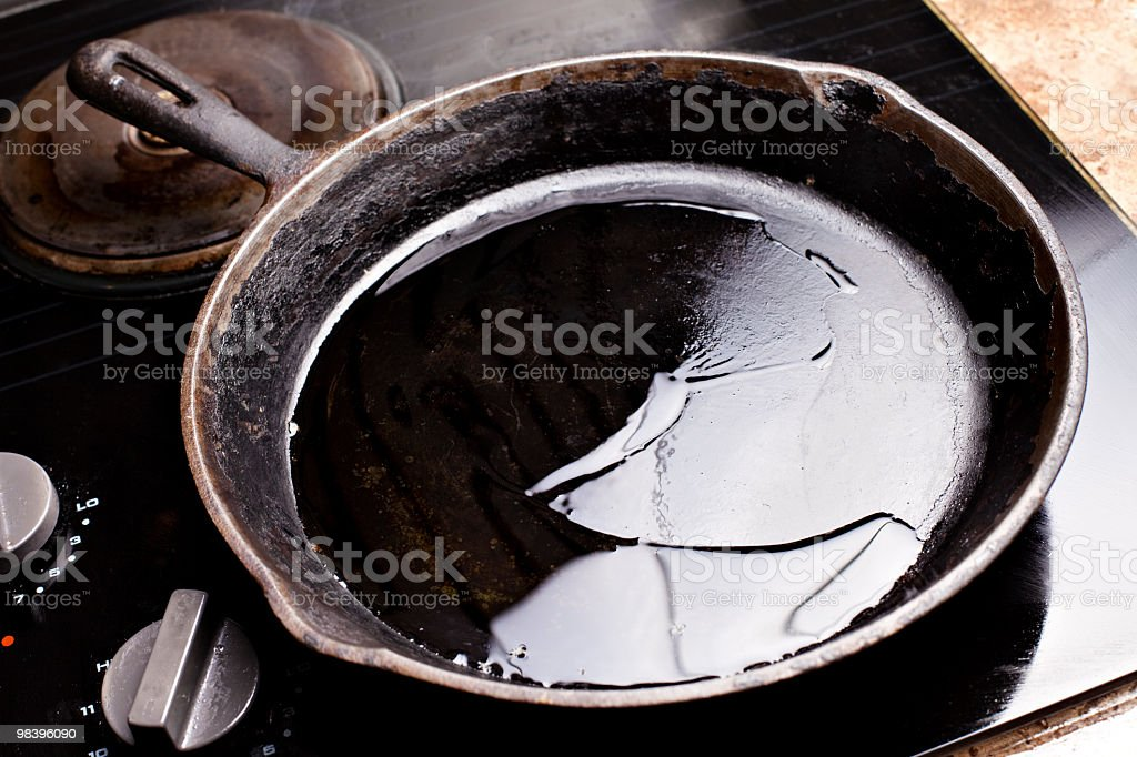 Old cast iron skillet with oil stock photo