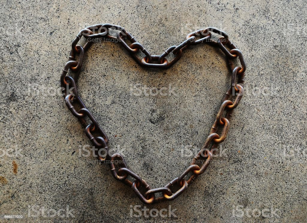 old chain heart-shaped on cememt floor stock photo