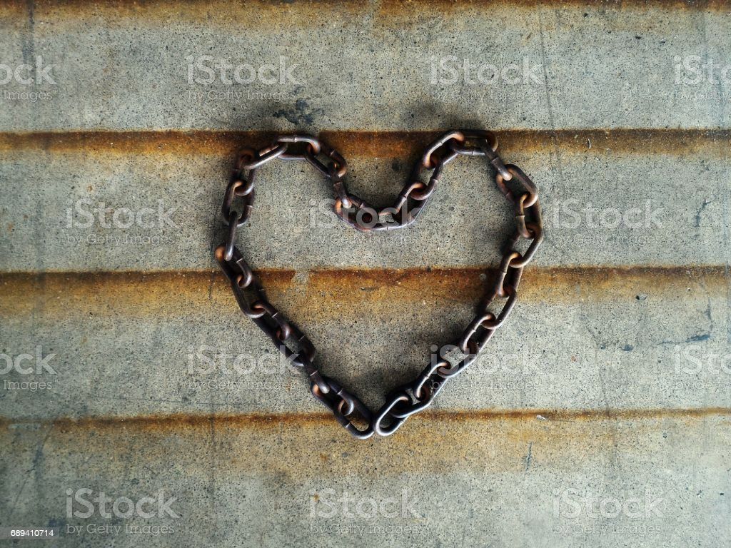 old chain heart-shaped on cement floor stock photo